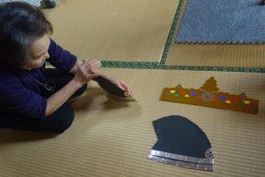 花まつりの稚児行列の衣装を準備する婦人会の方。被り物には、五環紋が折り紙で貼られている。