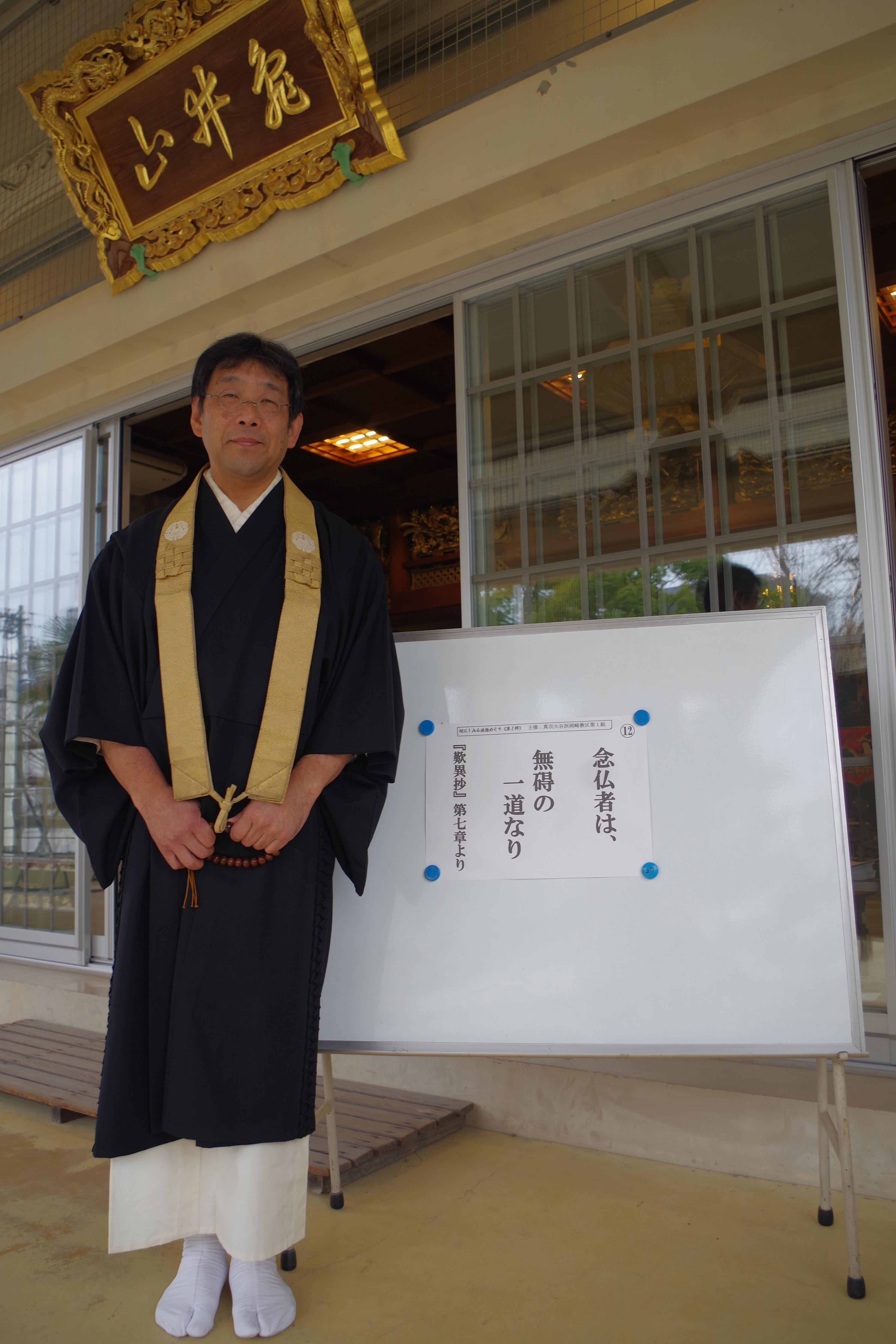 掲示板の前に立つ本田住職